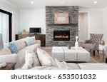 Beautiful living room interior with hardwood floors and fireplace in new luxury home. Couches at right angles face armchairs and fireplace surround stretches to ceiling and is bordered by credenza. - stock photo