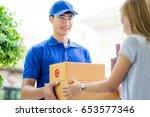 asian woman receiving a package ... | Shutterstock . vector #653577346