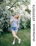 blonde girl in the summer park  | Shutterstock . vector #653595076