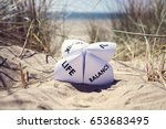 Small photo of Origami fortune teller on vacation at the beach concept for work life balance choices