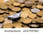 Small photo of origami of a boat sailing in a sea made of coin, italian adage that means be very rich, sailing on gold