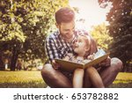 single father sitting on grass... | Shutterstock . vector #653782882