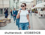 Small photo of Attractive girl in sunglasses walking along the street. White t-shirt. Mock-up.