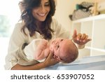 mother washing a newborn baby... | Shutterstock . vector #653907052