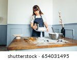 woman carefully icing the cake... | Shutterstock . vector #654031495