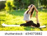 woman practicing yoga outdoors | Shutterstock . vector #654073882