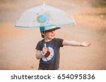little boy under umbrella | Shutterstock . vector #654095836