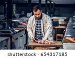 bearded butcher dressed in a... | Shutterstock . vector #654317185
