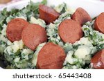 Dutch stamppot, mashed potatoes with kale, topped with vegetarian sausage. - stock photo