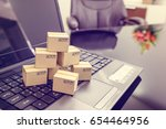 Small photo of Seven small paper boxes on a laptop keyboard. Concept of online shopping that shopper or buyer can procure or buy things from seller / retailer stores on the internet, purchasing can be done at home.