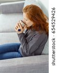 Small photo of Young woman savoring an enjoyable cup of coffee as she relaxes at home on a grey couch cradling the mug in her hands as she drinks, close up high angle view