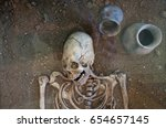 Small photo of Archaeological excavations of an ancient human homo sapiens man reasonable Neanderthal bones skeleton and human skull