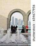 Small photo of DOHA, QATAR -20 DEC 2016- A group of Qatari women dressed in traditional black abaya robes admire the modern Doha skyline from inside the Museum of Islamic Art building located on the Doha Corniche.
