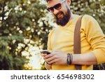 handsome man beard using... | Shutterstock . vector #654698302