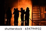 Silhouette Of Firemen Fighting...