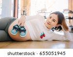 mom is holding little slippers... | Shutterstock . vector #655051945