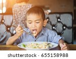 the boy sat and ate deliciously. | Shutterstock . vector #655158988
