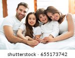 family of four lying on bed  | Shutterstock . vector #655173742