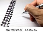 A hand holding a pen above a blank page of a spiral notebook. - stock photo