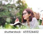 beautiful young woman writing... | Shutterstock . vector #655526602