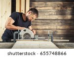 a man builder saws a board with ...   Shutterstock . vector #655748866