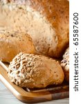 Rolls and loaf of bread on breadboard - stock photo