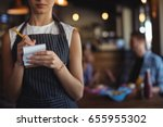 Small photo of Mid section of waitress taking order at restaurant
