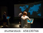 Small photo of January 5, 2017. Tourists interact with a projected display showing a blue, pixelated, world map at the Singapore National Museum. Travel and technology editorial concept.