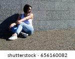 female sits on concrete floor... | Shutterstock . vector #656160082