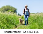 Stock photo mature woman with rucksack hiking with a dog in the summer landscape 656261116