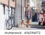 Stock photo woman walking with a dog at the leash in the city 656296072