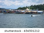 Small photo of An unidentified water taxi driver cruises along Kampong Ayer, Brunei's water village.