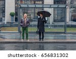 Two Men Stand At The Bus Stop ...