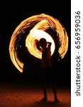 Small photo of Young boy in fire show spin alight flame in the dark night