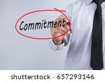 Small photo of Businessman Hand Writing commitment with a marker over transparent board, Business concept.