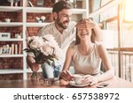 Stock photo surprise beautiful romantic couple in cafe young man is presenting flowers to his beloved feel 657538972
