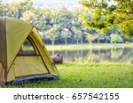 Camping green tent in forest near lake - stock photo