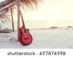 An acoustic guitar standing at the sandy beach under palm tree - stock photo