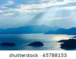 Ocean landscape with sunshine, islands and mountains - stock photo