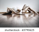 Young sexy sports woman stretching on floor. - stock photo