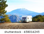 Caravan with a bike parked on a mountaintop with a view on the french Alps near lake Lac de Serre-Poncon on a bright sunny day - stock photo