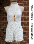 Small photo of Vertical image of mannequin with pretty white trendy romper and costume jewelry, set outside storefront