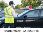 police officer giving a ticket... | Shutterstock . vector #658050748