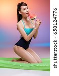 Small photo of Smiling young woman in swimsuit holding juicy watermelon while kneeling on air mattress