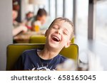 boy is laughing loudly in cafe | Shutterstock . vector #658165045