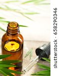 Small photo of tea tree oil in the amber glass bottle and fresh tea tree leaves