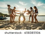 Small photo of Friends funny game on the beach under sunny sky with clouds at summer day.