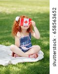 Small photo of Portrait of cute little red-haired Caucasian girl child holding Canadian flag with red maple leaf, sitting on grass in park outside, celebrating Canada Day anniversary