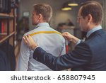 tailor measures a man in studio | Shutterstock . vector #658807945