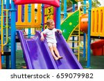 Small photo of Little boy is on the playground pulls down the pipe down, summer, happiness, vacation